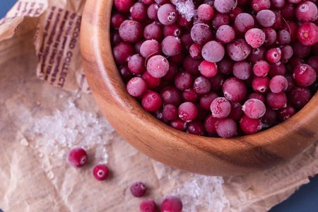 oude krant: Close up of frozen cranberries. Healthy frozen berries in wooden bowl on old newspaper.