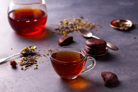 light slate gray: black tea in a transparent glass cup on grey stone table with glazed chocolate cookies and tea leafs.