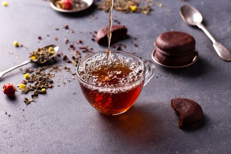 glass cup: black tea in a transparent glass cup on grey stone table with glazed chocolate cookies and tea leafs.