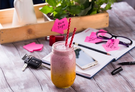 Healthy smoothie with business accessories. Young lady to do list for the day. Daily planner, glasses, pen, car keys and memory stickers on wooden table. Imagens