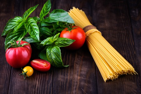 mediterranian style: Spaghetti and tomatoes with herbs on an old and vintage wooden table