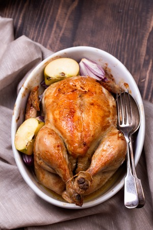shot: roasted chicken with apple in white ceramic pan, on wooden table, top view. Stock Photo