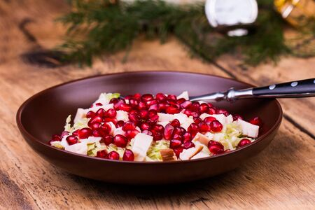 caper: Healthy salad with pomegranate seeds, chicken and cabbage. Old wooden table. Stock Photo