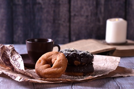 Tasty donuts on pack paper on wooden table with cup of coffee. Stock Photo