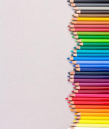 Veelkleurige potloden op beige pastelkleurdocument ruwe korrel grunge textuur