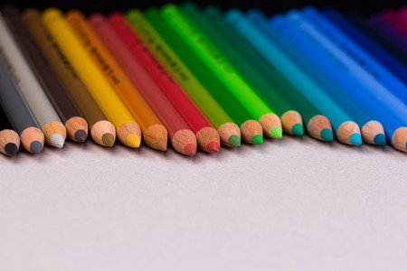 Multicolored pencils on beige pastel paper coarse grain grunge texture.