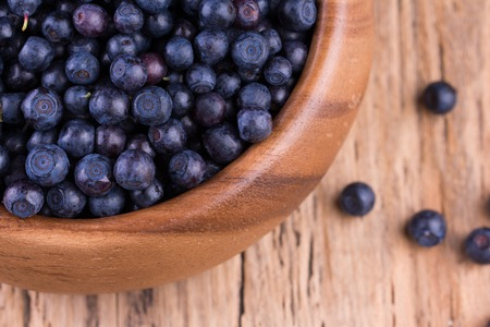 wildberry: Blueberries in a bowl on a vintage wooden table. Bilberry on wooden Background. Blueberry antioxidant. Stock Photo