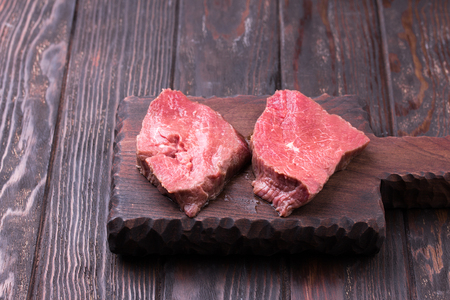 Raw beef steak ready for cooking on wooden cutting board. Wooden background.