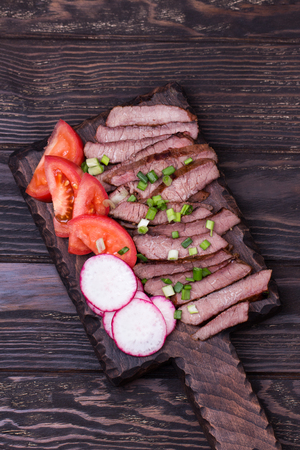 Grilled beef steak with spring onion, tomato and radish on cutting board. Top view