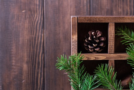 Christmas decoration. Pine cones and branches in box on wooden background