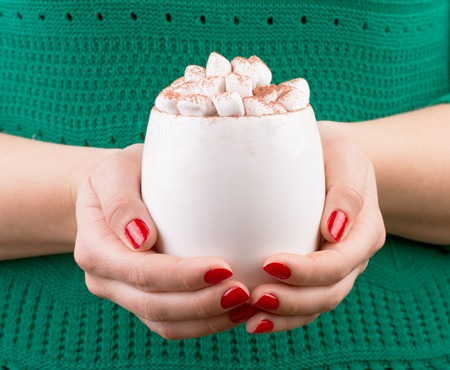 Female hand holding cup of hot cocoa or chocolate with marshmallow. Woman dressed in green knitted sweater