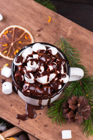 Christmas decoration. Hot chocolate with marshmallows, cinnamon and spices on a wooden board. Stock fotó