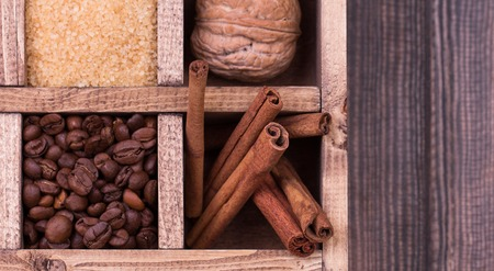 Christmas decoration. Gift box filled with christmas spices and nuts like cinnamon sticks, anise , nutmeg , brown sugar, hazelnut, coffee beans and walnut