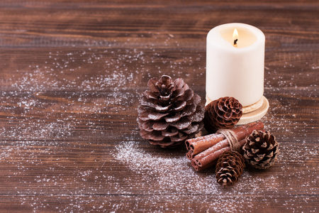 Christmas decoration. Candle, pine and fir cones with cinnamon sticks on wood table. Winter mood, holiday decoration.