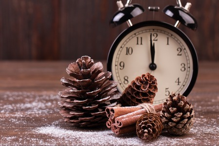New year decoration. New year clock and cones covered with snow. Selective focus.