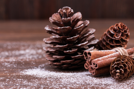 Christmas decoration. Pine and fir cones with cinnamon sticks on wood table. Winter mood, holiday decoration.