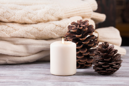 Christmas decoration. candle, cones and pile of white warm knitted sweater. Winter mood, holiday decoration. Stock fotó