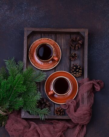 Two cups of coffee with christmas tree on a table.