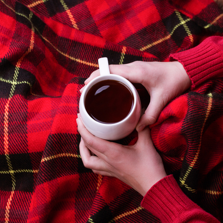 Hot mug of tea warming womans hands in red woollen sweater.