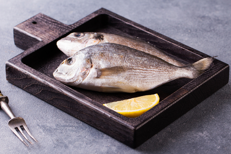 Fresh raw sea bream fish decorated with lemon slices Stock fotó