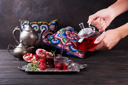 Fruit pomegranate tea in a teapot and cup. Turkish tea. Oriental tea ceremony concept. Archivio Fotografico