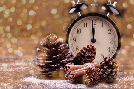 Decoración de año nuevo. Reloj de año nuevo y conos cubiertos de nieve. Enfoque selectivo Luces desenfocadas como fondo. Foto de archivo