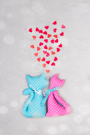 Blue and pink fabric toys - funny cute cats with heart shape confetti . Concept of Valentines day card. Handmade toys. Stock Photo