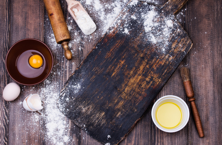 Baking background with free space for your text. Rolling pin, kitchen utensils, eggs and flour on black rustic bakery shovel . Copy space. Top view Stock fotó