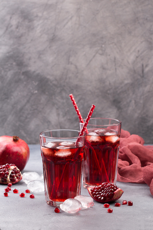 Fresh red lemonade with pomegranate and ice in glass on grey stone background. Summer drinks and cocktails Stock fotó