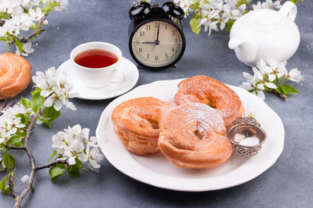 Powdered choux pastry with tea. Table decorated with apple blossom. Alarm clock as Time for breakfast concept.
