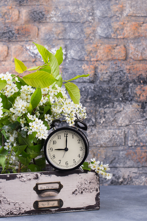 Alarm clock with spring blooming branch in wooden drawer against brick wall background. Time change concept. Spring time. Time management concept