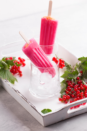 Pink berry ice pop with red currant on vintage background. Stock fotó