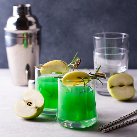 Green alcohol cocktail with apple and rosemary.