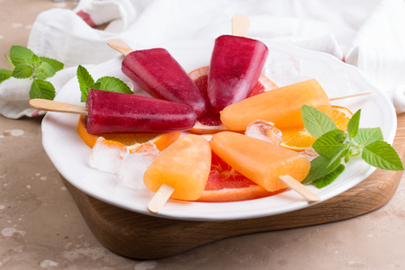 Pink and orange popsicle with red oranges on grey stone background.