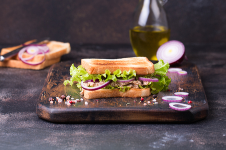 Tuna fish sandwich with onion, lettuce and olive oil on a wooden board. Stock fotó