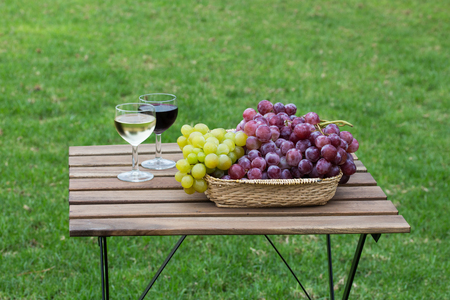 Tasty wine on wooden table on green lawn background