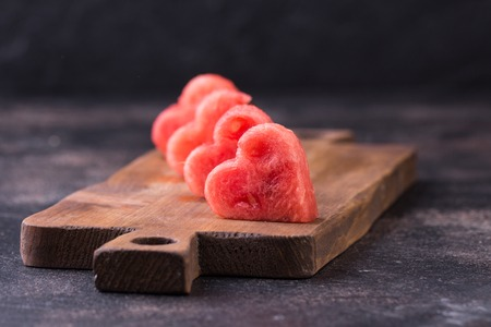 Heart shaped slices of watermelon cutout on old cutting board. Rustic dark table. Copy space. Healthy food concept.