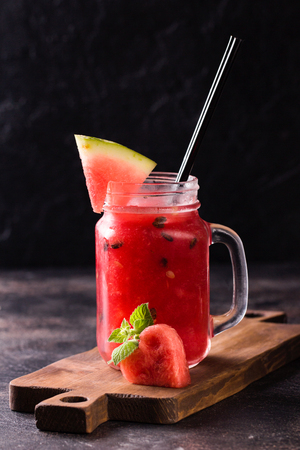 Fresh watermelon Smoothie in the Mason jar with heart shaped slice of watermelon on rustic dark background. Healthy food concept
