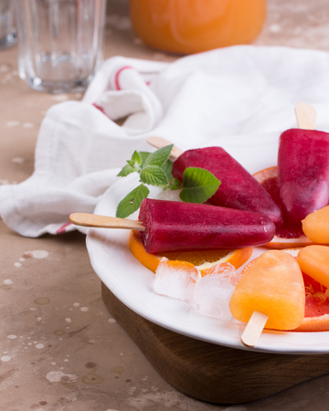Pink and orange popsicle on grey stone background.