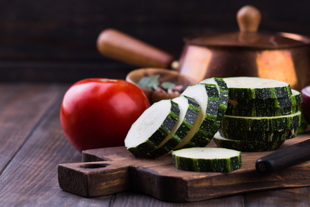 Zucchini with slices and onion on a wooden table.