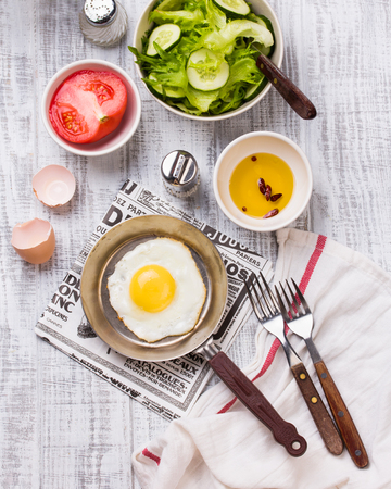 Fried eggs in a frying pan with tomatoes and vegetable salad for breakfast