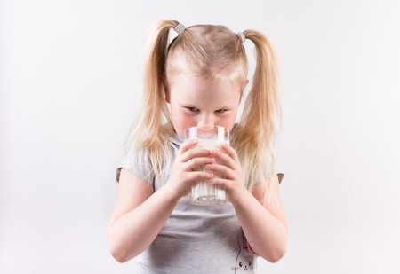 Young cute little blonde girl in light grey t-shirt smiling and holding glass of milk