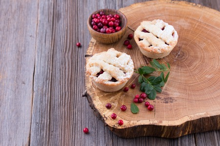 Homemade tartlet with cranberries on wooden table.