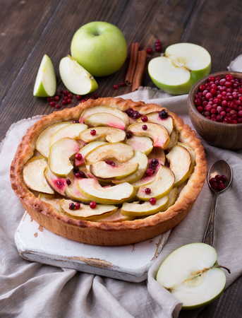 Homemade apple pie and ingredients on wooden