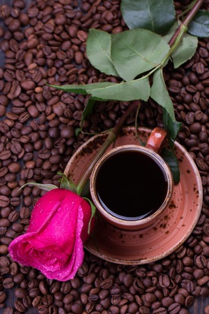 Mug of black coffee and rose on roasted coffee beans