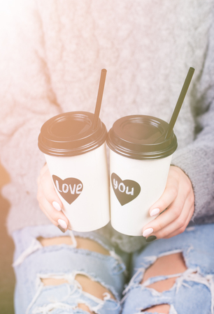 Young couple in warm sweaters and blue jeans with paper takeaway cups of coffee.