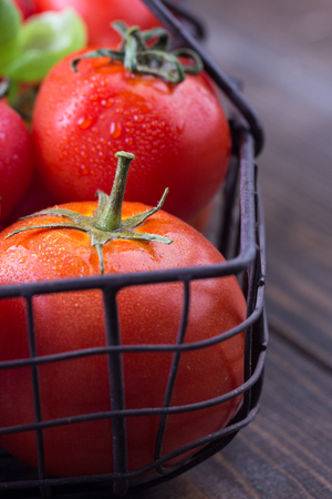 Fresh tomatoes in a iron basket on a dark wooden