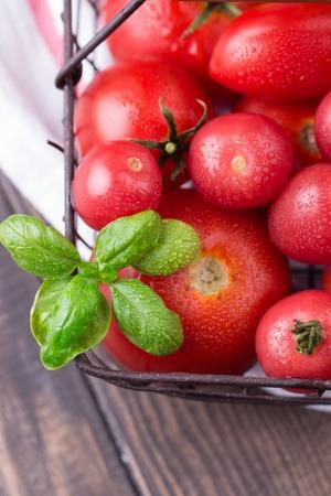 Pomodori freschi in un cesto di ferro su un legno scuro