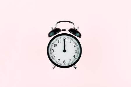 Black vintage alarm clock on vibrant color