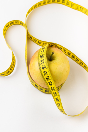 Flat lay composition with measuring tape and apple on white